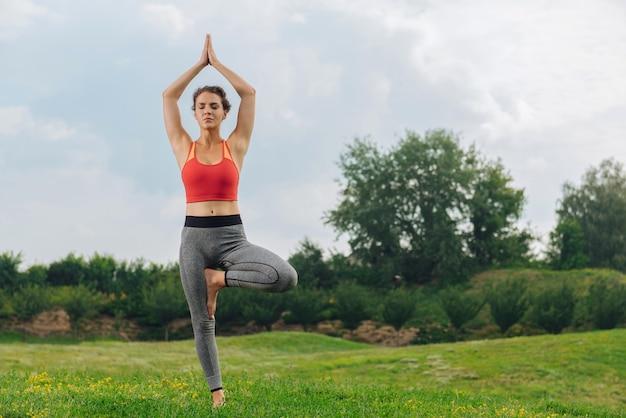 Спортивная (ый) красивая женщина закрыла глаза и медленно дышала во время занятий йогой на открытом воздухе