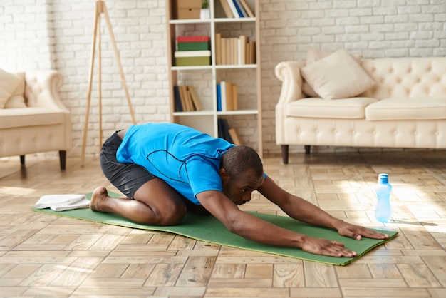 Athletic black man does advanced yoga on mat at home.