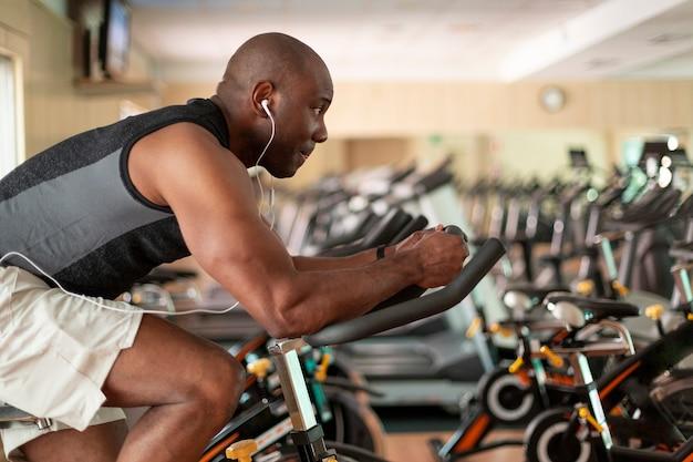 Спортивный (ый) темнокожий мужчина делает кардио-тренировку на велотренажере в тренажерном зале. понятие о спорте и здоровом образе жизни.
