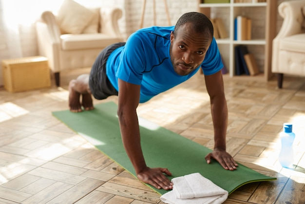 Athletic black man performs plank on mat at home.