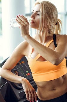 Athletic blond woman is drinking water on treadmill in gym.