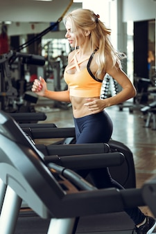 Athletic blond woman running on treadmill at gym