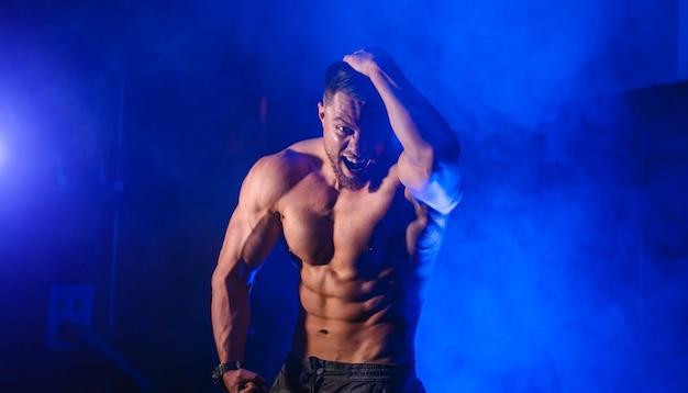 アスリートボディ。半回転のモデルの男は、濃い青の光の背景でカメラにポーズをとっています。強い筋肉の男。閉じる。