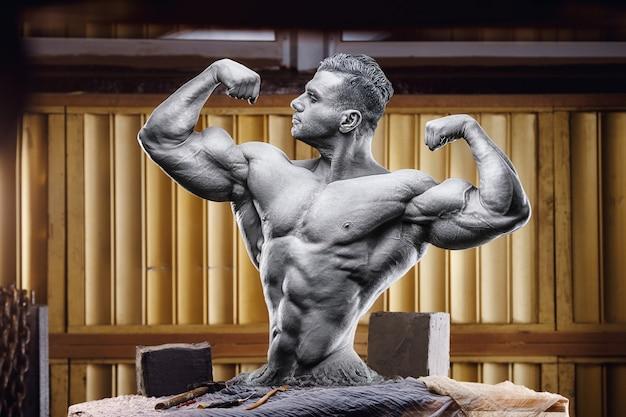 ワークショップスタジオの彫刻家の机の上の運動ボディービルダー像。ボディスカルプティング。自作の男。昔ながらのボディービルダー。ハンサムな白人スポーツマン。スポーツとオールドスクールのライフスタイル、80年代のコンセプト