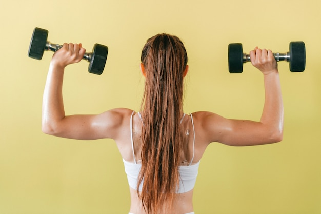 Athletic bodybuilder woman with dumbbells. long haired brunette girl with muscles lifting weights on yellow wall