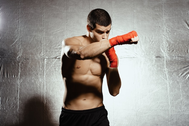 Athletic boxer punching with determination and precaution over silver kground