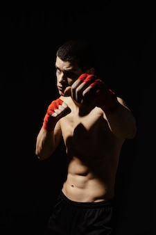 Athletic boxer punching with determination and precaution