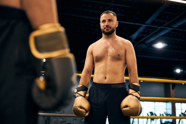 Athletic boxer with hairy chest standing in the ring looking at his opponent