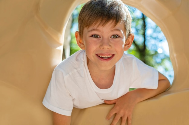Athletic boy child practicing rock climbing on climbing wall on playground. amusement park for kids