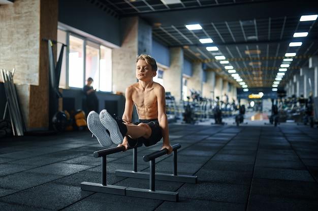 체육관에서 고르지 않은 막대에 abs 운동을 하 고 체육 소년. 스포츠 클럽, 건강 관리 및 건강한 라이프 스타일 훈련, 에어로빅 운동 모범생, 낚시를 좋아하는 청소년