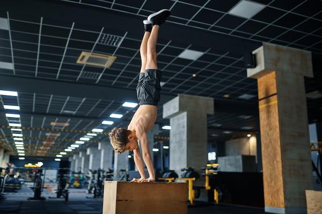 그의 손에 서 운동 소년, 체육관에서 받침대에 균형 운동. 스포츠 클럽, 건강 관리 및 건강한 라이프 스타일 훈련, 에어로빅 운동 모범생, 낚시를 좋아하는 청소년