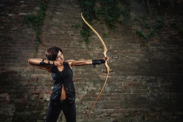 Атлетик брюнетка девушка в черном стрельба из лука.