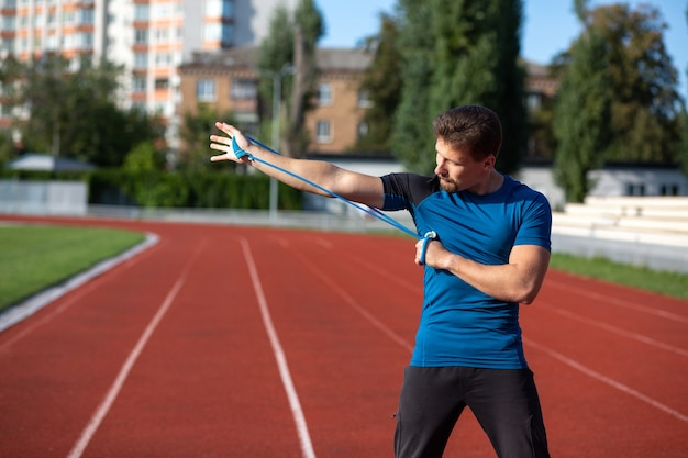 Athletic brunette man doing workout with elastic expander at the stadium in sunny day. empty space