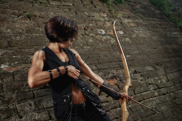 Athletic brunette shooting with bow and tacking focus.