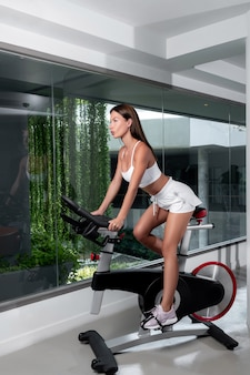 Athletic brunette in a white top and white short shorts posing while sitting on an exercise bike