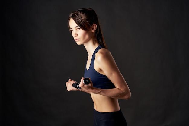 Athletic brunette with dumbbells in her hands slim figure exercise motivation