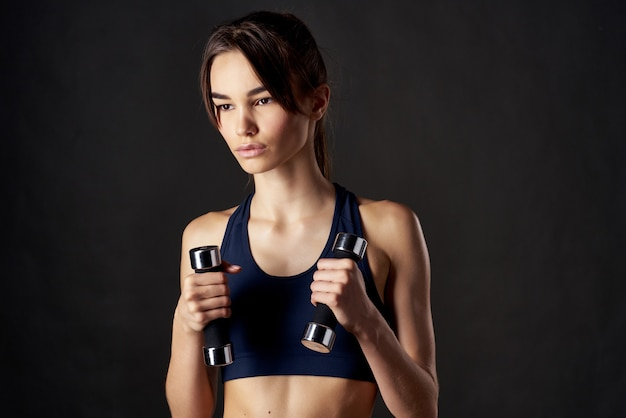 彼女の手にダンベルを持ったアスレチックブルネットスリムな体型運動のモチベーション。高品質の写真