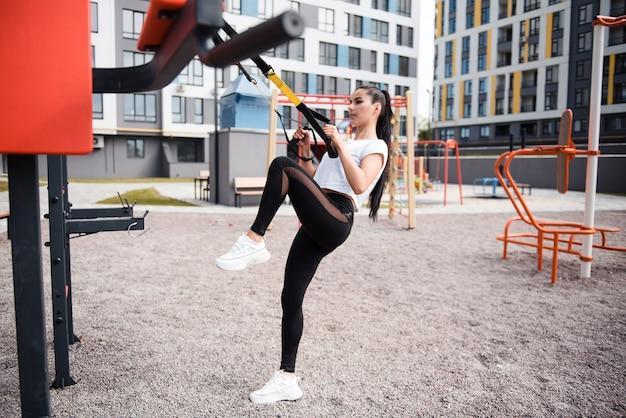 Спортивная брюнетка в белой футболке днем тренируется с помощью фитнес-ремней на детской площадке