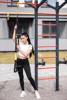 Спортивная (ый) женщина брюнет в белой футболке стоя на спортивной площадке и держа ремни фитнеса. тренировка на открытом воздухе, портрет красивой спортивной брюнетки.