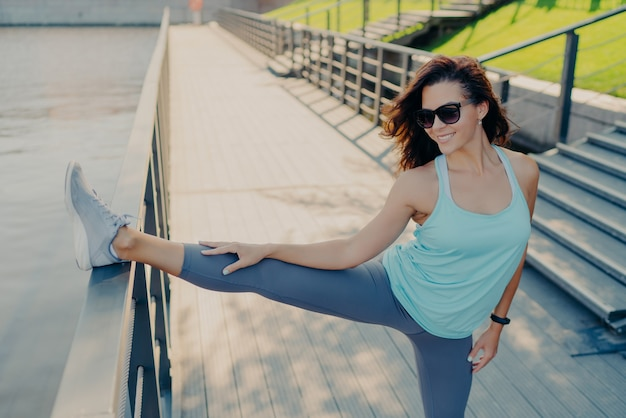 Athletic brunette woman stretches legs wears sunglasses t shirt leggings and sneakers has slim figure prepares for workou outdoors leads sporty lifestyle. people flexibility and exercising concept