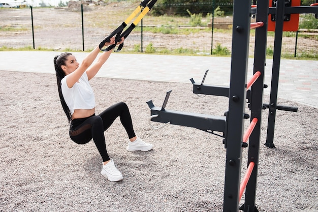 Athletic brunette woman in a white tshirt during the day trains with the help of fitness straps on the playground