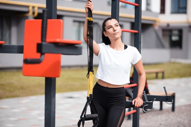 Athletic brunette woman in a white tshirt standing on the playground and holding fitness straps. outdoor workout, portrait of beautiful sporty brunette.