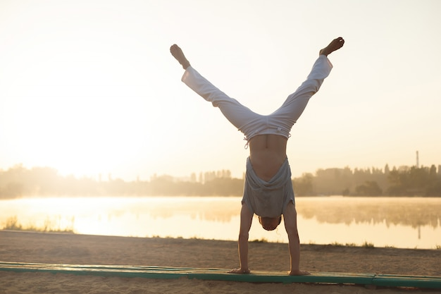 Athletic capoeira performer workout training on the beach sunrise