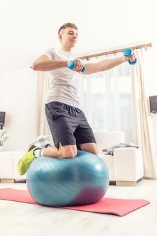 운동 백인 청년은 한 팔을 손에 아령으로 뻗은 채 똑바로 자세를 잡고 있는 피트니스 공에 무릎을 꿇고 있습니다.