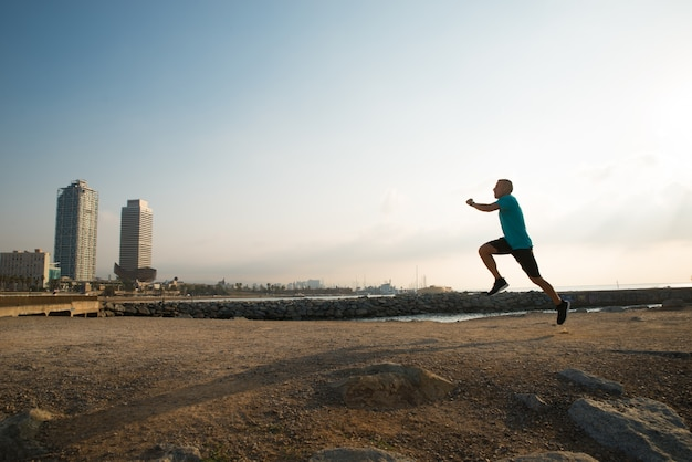 Athletic city guy running in morning