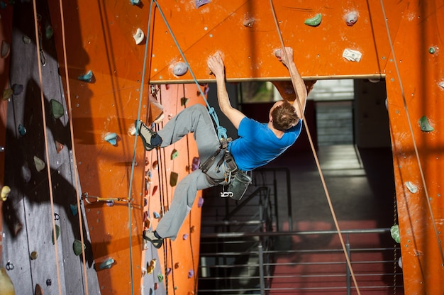 Athletic climber climbs on an indoor rock-climbing wall with special equipment