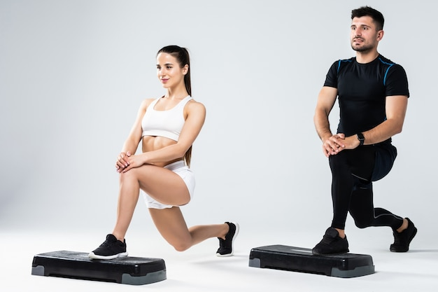 Athletic couple doing exercises over steps in aerobic class isolated on white background