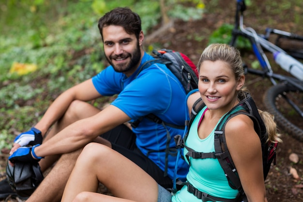 Athletic couple relaxing in forest