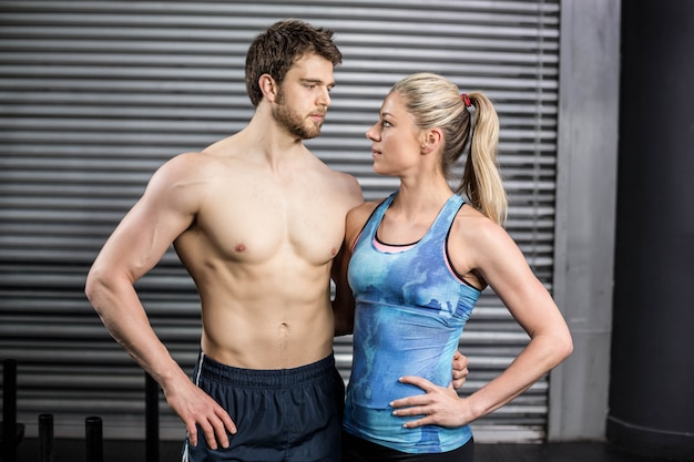 Athletic couple staring into each other in the eyes at gym