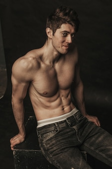 Athletic cute man posing topless in jeans.