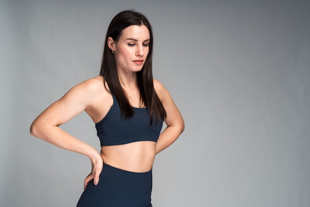 スポーツウェアを着た運動の黒髪の女性は、有酸素運動の後に休憩を取りながら脇に集中しました。しんみりと遠くを見つめる少女