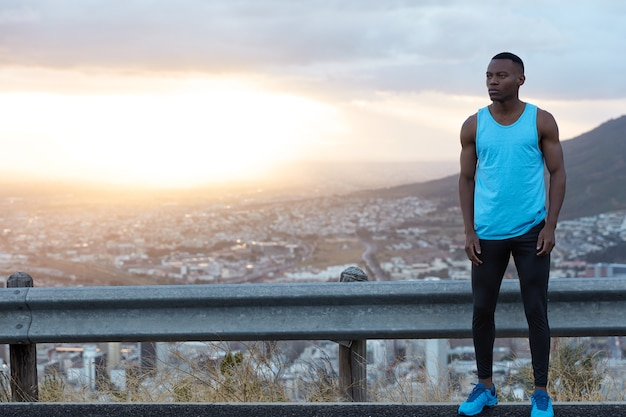 L'uomo atletico dalla pelle scura indossa abiti casual comodi, si riposa dopo un allenamento fitness attivo, ama gli esercizi fisici, concentrato a distanza, ha la pelle scura, le labbra carnose. copi lo spazio sopra la vista della natura