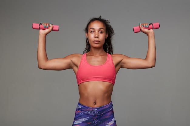 Спортивная темнокожая женщина с вьющимися длинными каштановыми волосами делает тренировку для рук стоя, одетая в спортивную одежду
