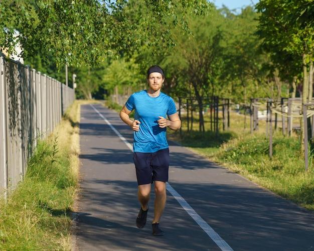 Спортивный (ый) европейский мужчина в спортивной одежде на пробежке по дороге в зеленом парке в прекрасный летний день