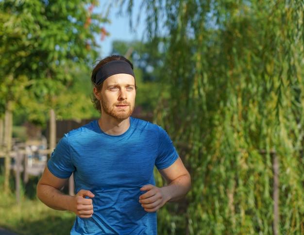 Спортивный (ый) европейский мужчина в спортивной одежде бегает по дороге в зеленом парке в прекрасный летний день
