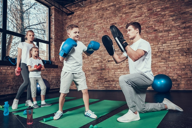 Атлетическая семья в перчатках тренируется в спортзале.