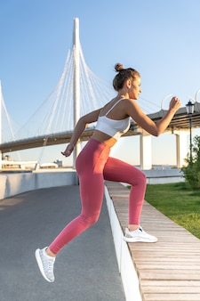 Athletic female doing step cardio exercises outdoors with a bridge and a river in the background