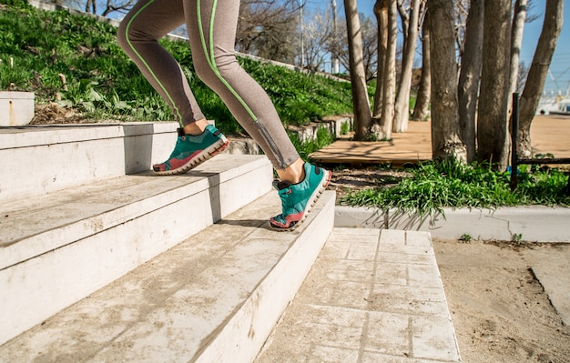 Athletic female legs climb the stairs