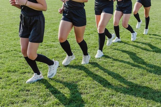 Athletic female legs jogging on grass