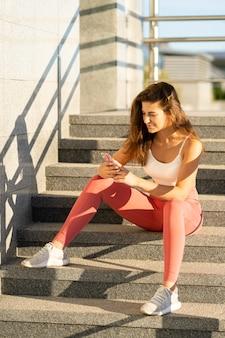 屋外の階段に座って運動する女性が携帯電話を使う