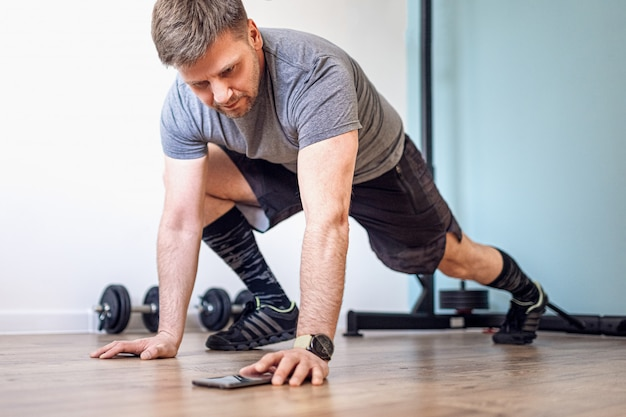 Athletic fit man in t-shirt and shorts is doing mountain climber exercises