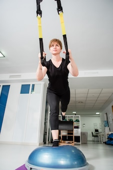 Athletic fit woman makes trx exercise