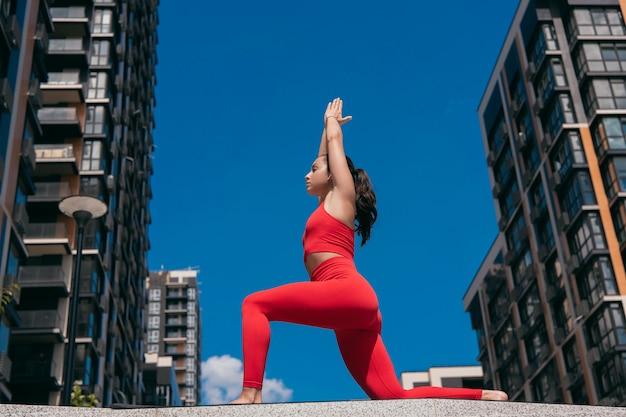 アスレチックフィットの女性の練習腕を上げた低ランジポーズ