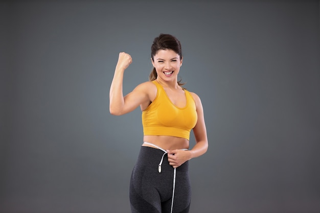 An athletic fit woman in sportswear in front of a gray wall measuring her waist with a tape