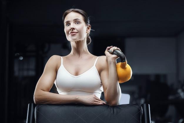 ケトルベルで筋肉をポンピングジムでトレーニング中のアスレチックフィットネス女性。フィットネスとスポーツのコンセプト