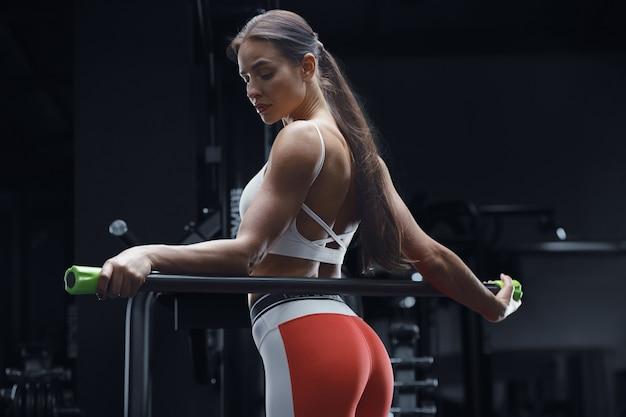 筋肉を伸ばすボディバーとジムでトレーニング中のアスレチックフィットネス女性。フィットネスとスポーツのコンセプト。ジムで腹筋運動をしている白人のボディービルダー